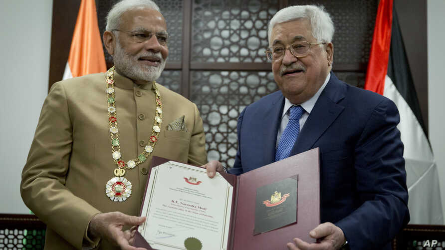 Palestinian President Mahmoud Abbas, right, decorates Indian Prime Minister Narendra Modi with the Grand Collar of the State of Palestine medal, during his visit to the Palestinian Authority headquarters in the West Bank city of Ramallah, Feb. 10, 20