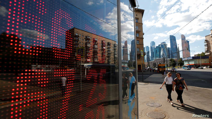 Pedestrians walk past an electronic board showing currency exchange rates of the U.S. dollar and euro against Russian ruble in Moscow, Aug. 10, 2018.