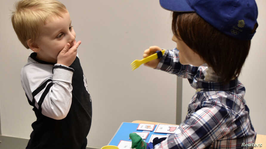 Harrison, 5, who is autistic, plays with Kaspar, a child-sized humanoid robot developed at the University of Hertfordshire to interact and help improve the lives of children with autism, in Stevenage, Britain, Jan. 30, 2017.