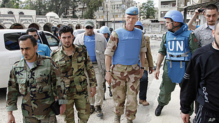The Chief of the U.N. Supervision Mission to Syria, Norwegian Major General Robert Mood (2nd R) and his team walk with members of the Free Syrian Army, at the Khalidiya neighborhood during the United Nations observers' visit to Homs, May 3, 2012.