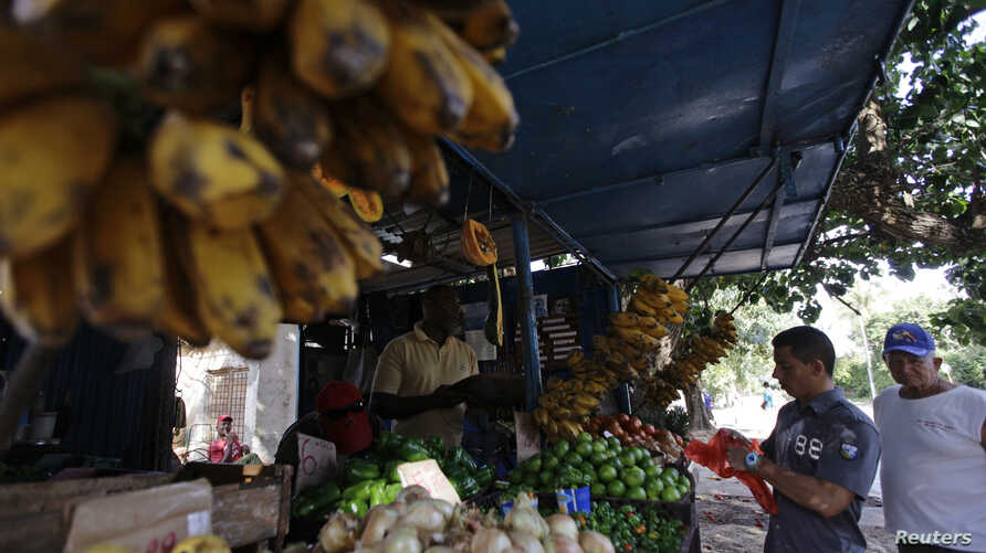 FILE - People buy food at a privately-licensed fruit and vegetable stall in Havana, Cuba, Feb. 1, 2012.