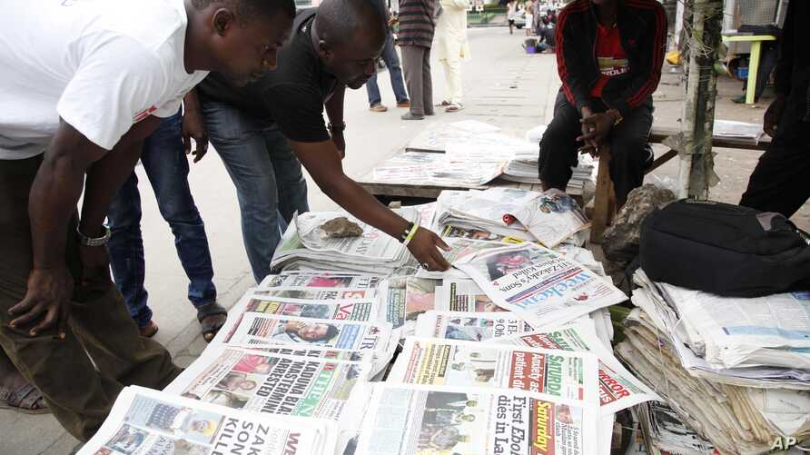 FILE - Men read newspapers on a street in Lagos, Nigeria, July 26, 2014. Military officers have seized newspapers from newsstands in the city of Aba for reportedly publishing materials aimed at inciting readers.