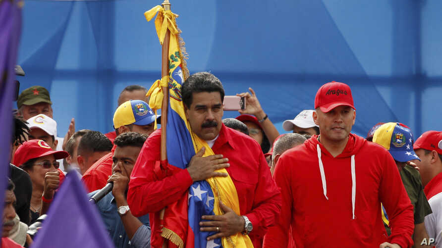 "Venezuela's President Nicolas Maduro holds the Venezuelan flag next to singer ""El Potro Alvarez"" during a rally in Caracas, Venezuela, July 27, 2017."