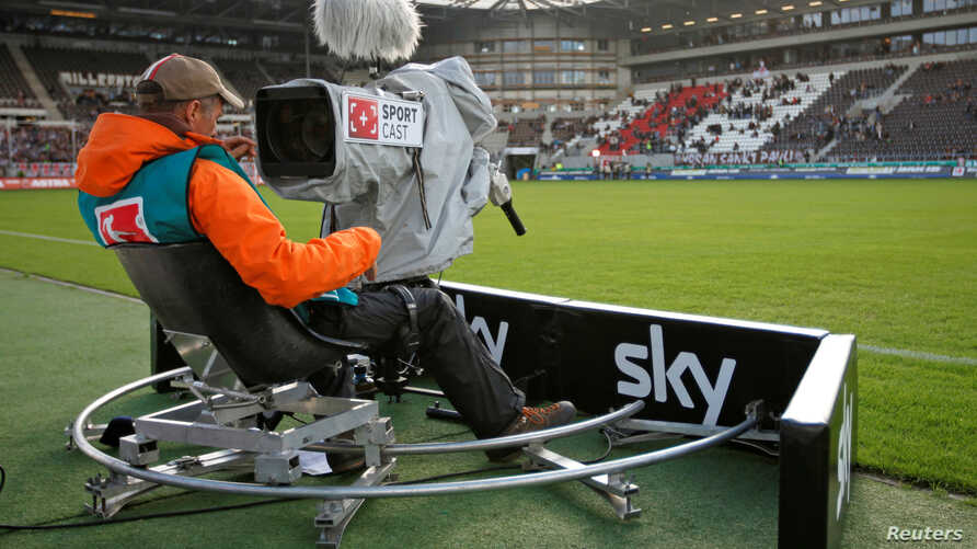 FILE - TV camera operator with the Sky television team checks his camera before a soccer match in Hamburg, August 28, 2010.