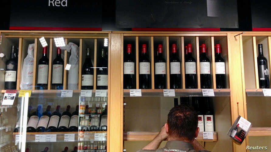 FILE - Bottles of Penfolds Grange, made by Australian wine maker Penfolds and owned by Australia's Treasury Wine Estates, are displayed as a shop assistant places more wine bottles onto shelves below at a wine shop in central Sydney, Australia, Aug.