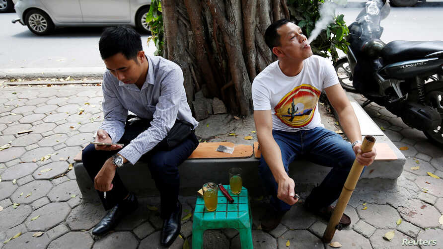 FILE - A man smokes from a bamboo pipe as another holds a cigarette on a street in Hanoi, Vietnam, May 11, 2017.