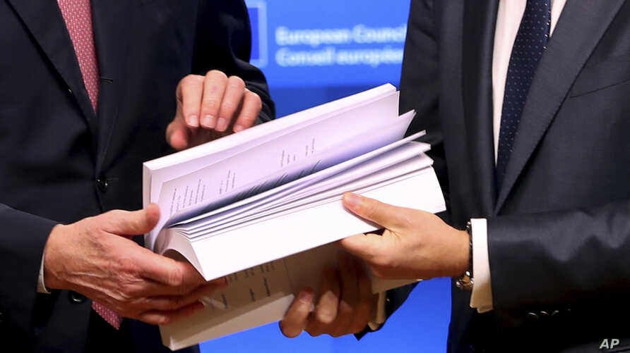 EU chief Brexit negotiator Michel Barnier, left, and European Council President Donald Tusk flip through the pages of a draft withdrawal agreement at the Europa building in Brussels, Nov. 15, 2018.