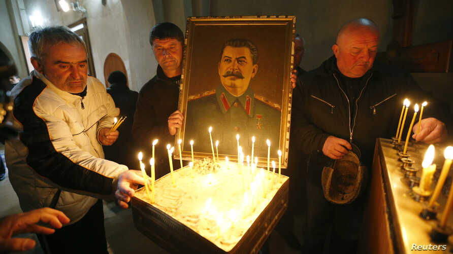 FILE - People place candles inside a church during a gathering to mark the anniversary of Soviet leader Joseph Stalin's death in his hometown of Gori, Georgia, March 5, 2017.