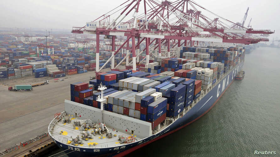 A cargo ship loaded with containers is seen anchored at a port in Qingdao, Shandong province, China, July 10, 2013.
