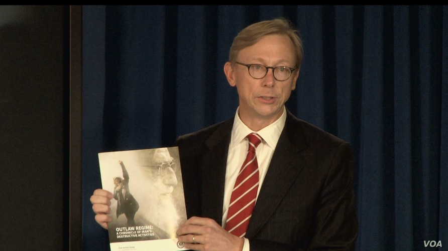 "U.S. Special Representative for Iran Brian Hook speaks at a Sept. 28, 2018, press briefing in New York, holding a copy of the State Department's Sept. 25 report ""Outlaw Regime: A Chronicle of Iran's Destructive Activities."""