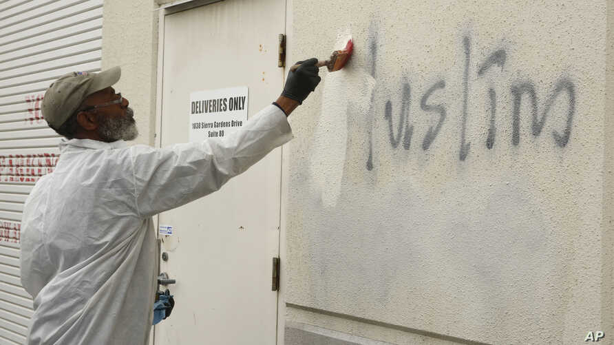 """A man paints over racist graffiti, which included such pronouncements as """"Muslims out,"""" on the side of a mosque in what officials are calling an apparent hate crime, in Roseville, California, Feb. 1, 2017."""