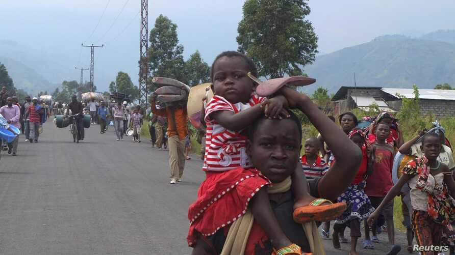 Displaced families flee renewed fighting between the Congolese Revolutionary Army (CRA) and Congolese army in Mugunga, near Goma, November 22, 2012.