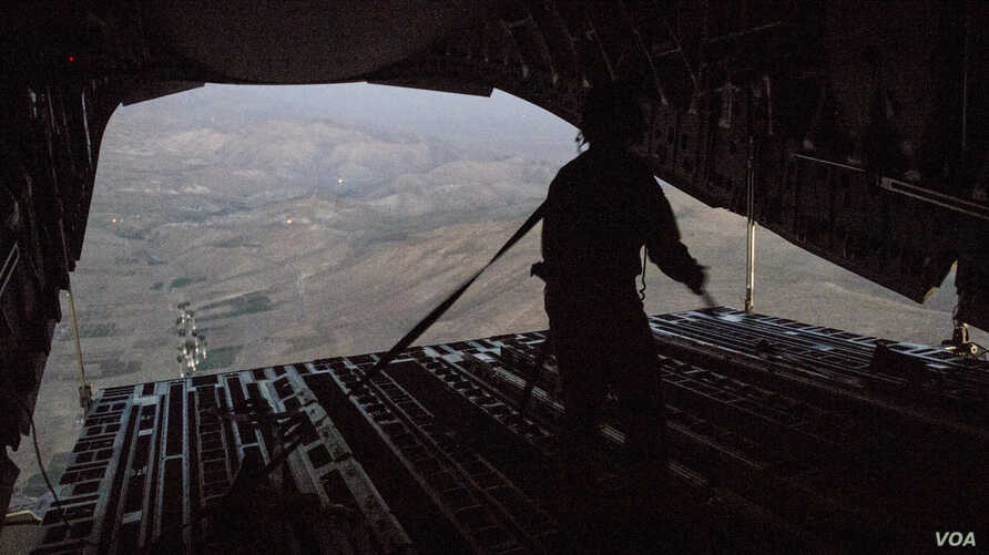 Tech. Sgt. Lynn Morelly, 816th Expeditionary Airlift Squadron, C-17 Globemaster III loadmaster, watches bundles of halal meals parachute to the ground during a humanitarian airdrop mission over Iraq, Aug. 9, 2014. To date, in coordination with the go