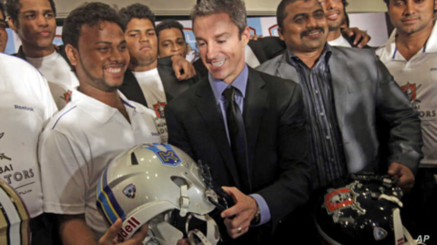 Chief Executive Officer of Elite Football League India Richard Whelan, center, poses with Indian players during a press conference to announce the league in Mumbai, India, Aug. 5, 2011.
