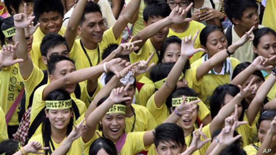 Students flash the 'L' sign for Laban or Fight as they join the march celebrating the 25th anniversary of People Power revolution, February 25, 2011 in suburban Pasig City east of Manila, Philippines
