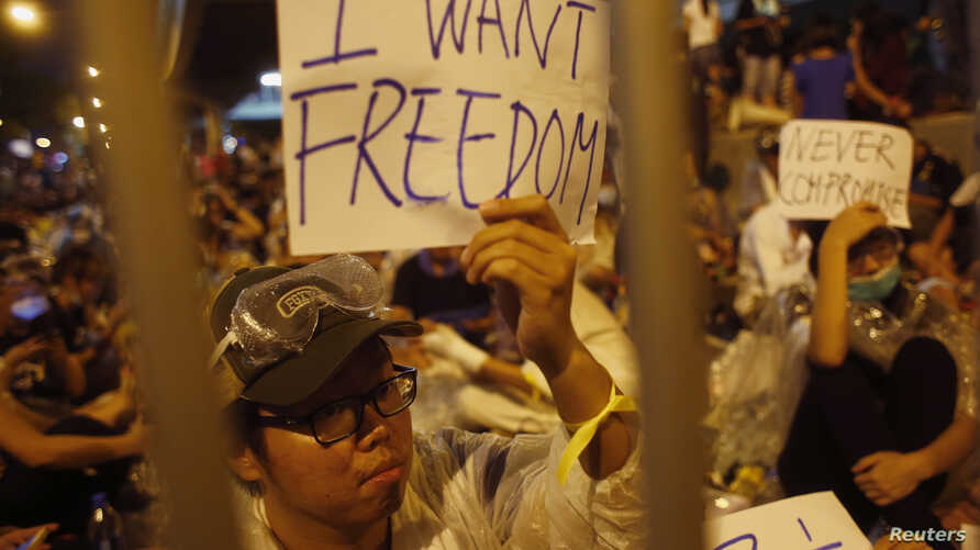 Protesters hold up signs during an evening rally attended by thousands in front of the government headquarters in Hong Kong, Sept. 27, 2014.