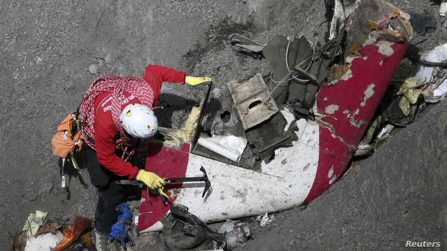 A French rescue worker inspects the remains of the Germanwings Airbus A320 at the site of the crash, near Seyne-les-Alpes, French Alps, March 29, 2015.
