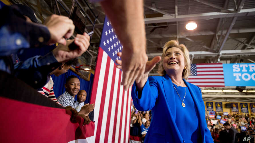 Democratic presidential candidate Hillary Clinton greets a member of the audience as she arrives to speak at a rally at Johnson C. Smith University in Charlotte, N.C., Sept. 8, 2016.
