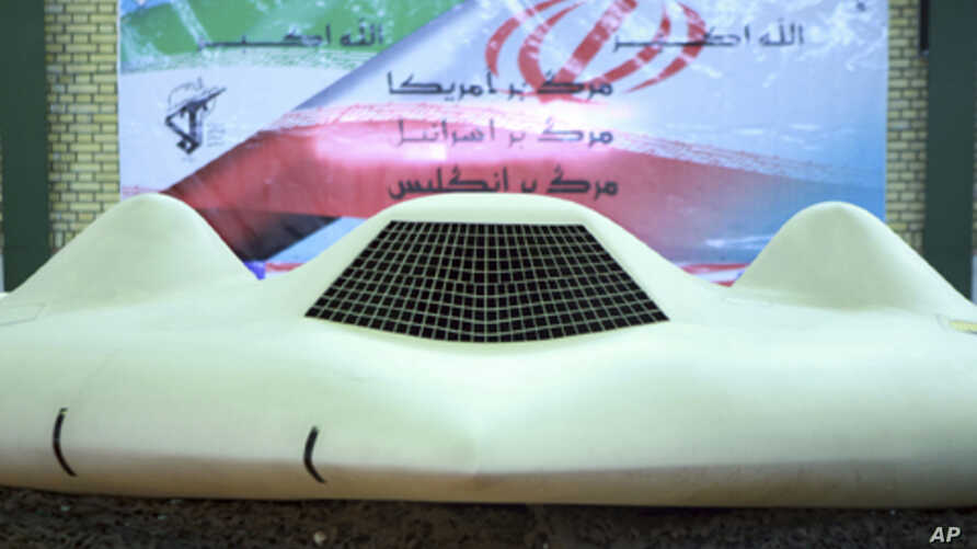 This photo released on Thursday, Dec. 8, 2011, by the Iranian Revolutionary Guards and taken at an undisclosed location claims to show the US RQ-170 Sentinel drone which Tehran says its forces downed earlier this week. In the banner in background dep