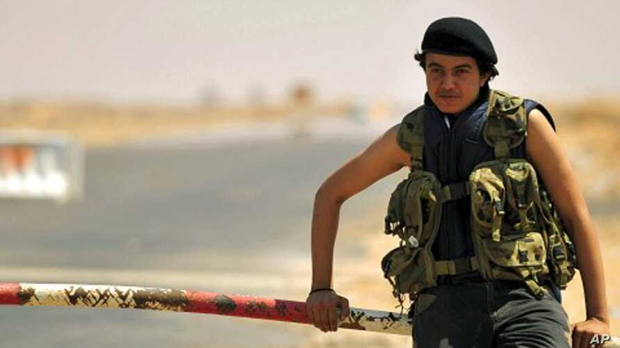A Libyan rebel stands near the entrance of Ras Lanuf oil refinery August 27, 2011