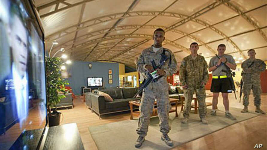 Spc. Gavin Fruge, 22, of Crowley, La., left, watches a rebroadcast of President Barack Obama's speech on proposed troop withdrawal with fellow soldiers at Kandahar Airfield in Kandahar, Afghanistan, June 23, 2011 (file photo)