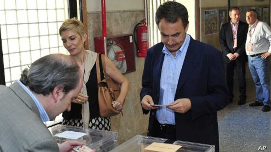 An official checks Spain's Prime Minister Jose Luis Rodriguez Zapatero's identification before voting, with his wife Sonsoles Espinosa at left, at a voting center in Madrid, May 22, 2011
