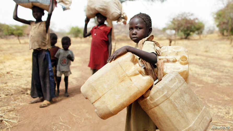 Children carry their family's belongings as they go to Yida refugee camp in South Sudan outside Tess village in the rebel-held territory of the Nuba Mountains in South Kordofan, May 2, 2012.