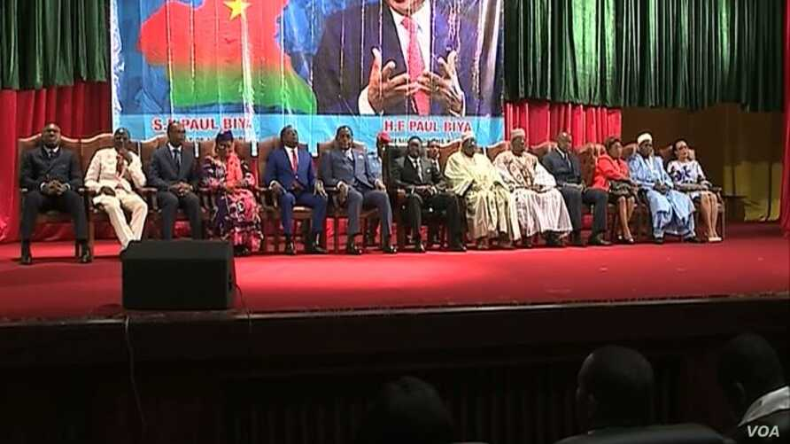 Government ministers sit under a banner depicting Cameroonian President Paul Biya during celebrations marking Biya's 86th birthday, at Yaounde Conference Center, in Yaounde, Cameroon, Feb 13, 2019.