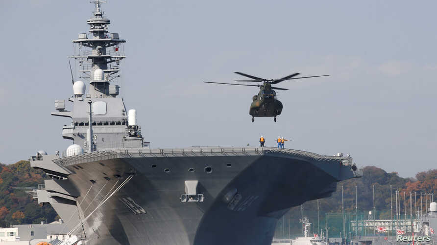 FILE - A helicopter lands on the Izumo, Japan Maritime Self Defense Force's (JMSDF) helicopter carrier, at JMSDF Yokosuka base in Yokosuka, south of Tokyo, Japan, Dec. 6, 2016.