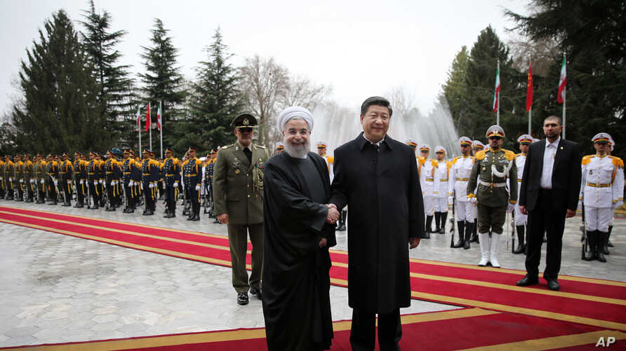 Chinese President Xi Jinping, center right, shakes hands with Iranian President Hassan Rouhani, as they pose for a photograph in an official arrival ceremony, at the Saadabad Palace in Tehran, Iran, Jan. 23, 2016.