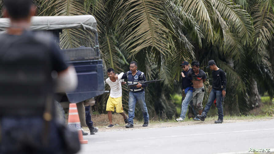 Malaysian police detain two men March 6, 2013, when they were coming out from Tanjung Labian, a village adjacent to Kampung Tanduo, a village adjacent to Kampung Tanduo, where Malaysian troops stormed the camp of an armed Filipino group on Tuesday.