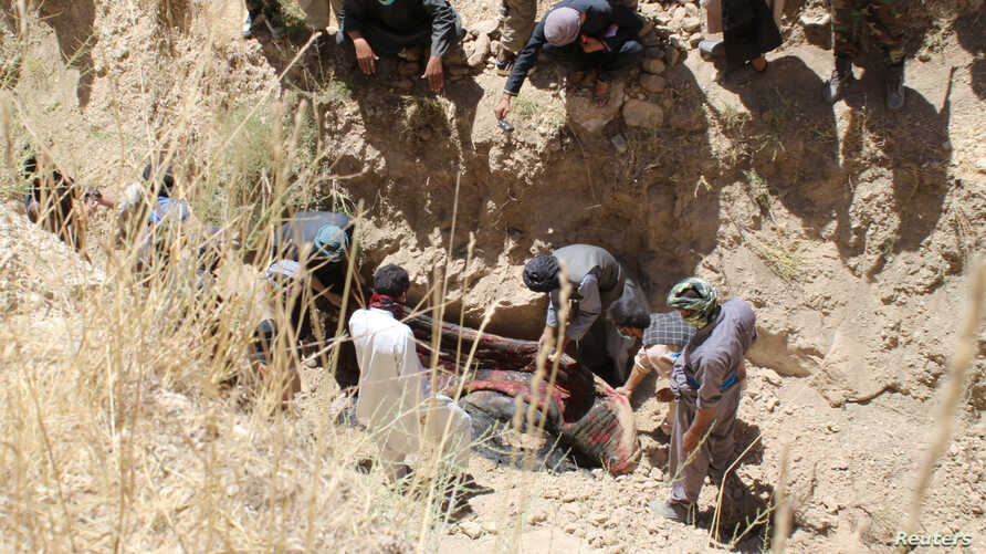 Villagers collect the dead bodies of civilians who were killed by insurgents at Mirza Olang village, in Sar-e Pul province, Afghanistan Aug. 15, 2017.