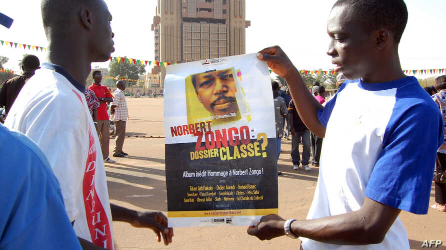 Demonstrators show a poster with a portrait of late journalist Norbert Zongo on December 13, 2008 during a protest in Ouagadougo against the impunity in the case of Burkinabe journalist Norbert Zongo, who was killed ten years ago. The march has been