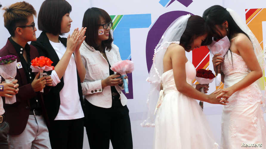 Newly married same-sex couple Tran Ngoc Diem Hang (R) and Le Thuy Linh (2nd R) during their public wedding as part of a lesbian, gay, bisexual, and transgender (LGBT) event on a street in Hanoi Oct. 27, 2013.