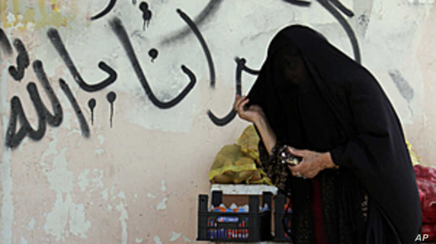 "A Bahraini woman shops for produce on Tuesday, October 4, 2011, in the Shi'ite Muslim village of Malkiya, Bahrain. The graffiti on the wall behind her reads: ""God, free our prisoners."""
