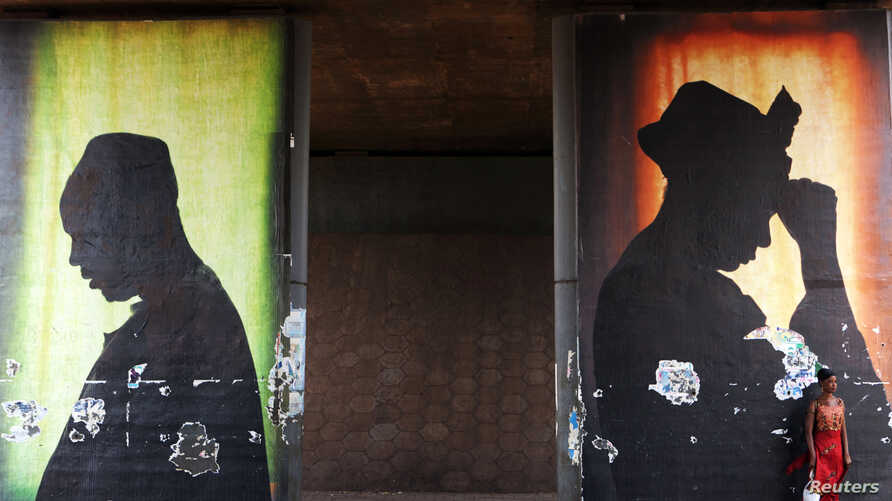 A woman stands in front of a poster in Bamako, Mali, Feb. 21, 2014.