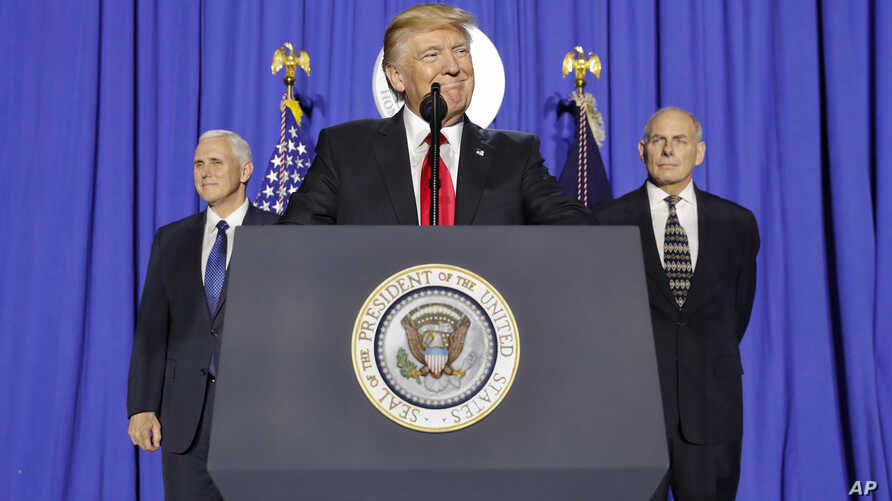 President Donald Trump, accompanied by Vice President Mike Pence, left, and Homeland Security Secretary John F. Kelly, pauses while speaking at the Homeland Security Department in Washington, Jan. 25, 2017.
