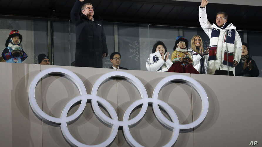 Thomas Bach, president of the International Olympic Committee, and South Korean President Moon Jae-in wave during the closing ceremony of the 2018 Winter Olympics in Pyeongchang, South Korea, Feb. 25, 2018.