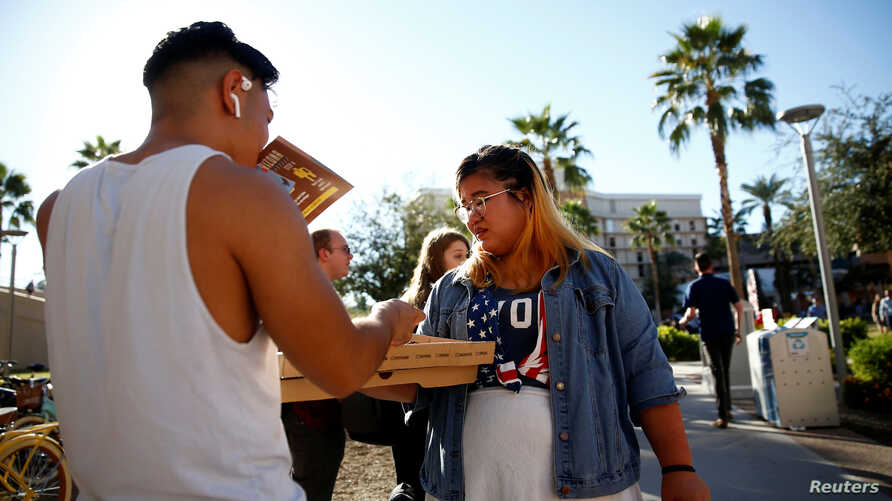 Kathryn Quintin of the policy and education group Young Invincibles, right, offers free pizza to students waiting in line to vote at the ASU Palo Verde West polling station during the U.S. midterm elections in Tempe, Ariz.. Nov. 6, 2018.