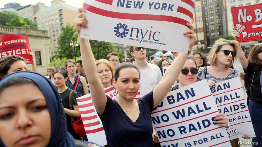 FILE PHOTO: Protesters hold signs against U.S. President Donald Trump's limited travel ban, approved by the U.S. Supreme Court, in New York City, on June 29, 2017.