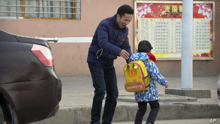 In this Dec. 18, 2017, photo, Chinese labor activist Hua Haifeng, adjusts the backpack of his son Bo Bo, 4, as he takes him to school on the outskirts of Xiangyang in central China's Hubei Province.