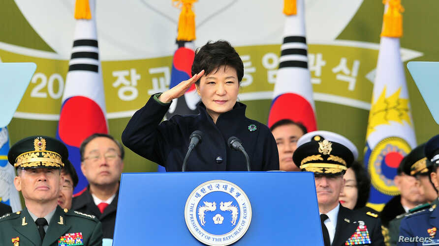 caption2: South Korean President Park Geun-hye salutes during a joint commissioning ceremony for 5,860 new officers from the Army, Navy, Air Force and Marines at the military headquarters in Gyeryong, south of Seoul, March 6, 2014.