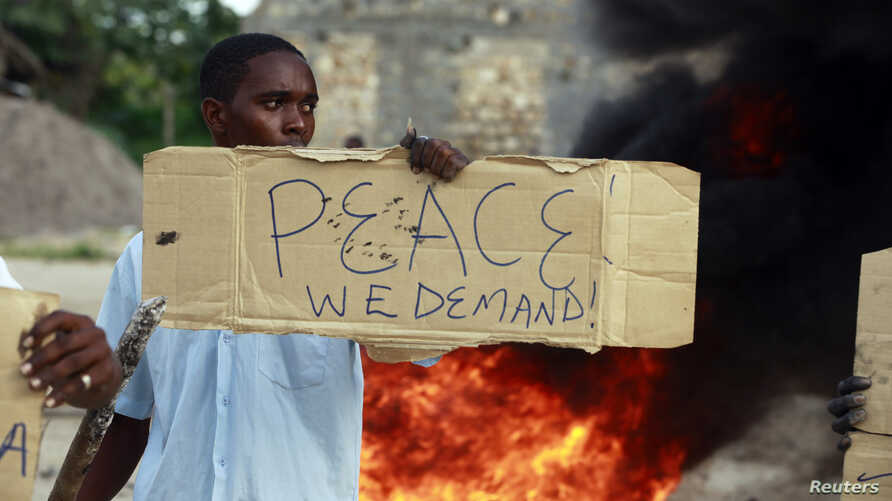 A resident holds a sign as he participates in a protest against the recent attack by gunmen in the coastal Kenyan town of Mpeketoni, June 17, 2014.