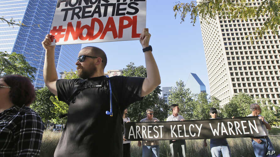 Jeremy Browning holds a sign while protesting with others outside the federal building housing the Army Corps of Engineers offices in Dallas, Nov. 15, 2016. People across the U.S. have gathered to show solidarity with opponents of the Dakota Access o