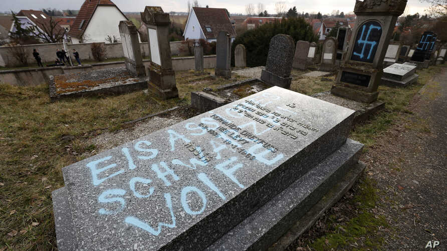 """A graffiti reads """"Black wolves form Alsace"""", referring to radical group from the 1970-1980s, is written on a tomb of the Jewish cemetery in Quatzenheim, eastern France, Feb.19, 2019."""