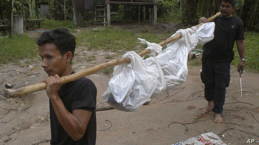 Workers carry a dead body in Songkhla province, southern Thailand, May 1, 2015. Police in Thailand found dozens of shallow graves in an isolated mountain area believed to have been used a trafficking camp.