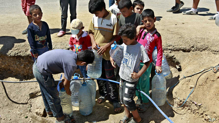Syrian refugees fill up water bottles at a temporary refugee camp in the eastern Lebanese town of Faour near the border with Syria, August 28, 2013.