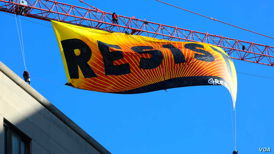 """Greenpeace protesters unfurl a banner on a construction crane reading """"RESIST,"""" just blocks from the White House in downtown Washington, D.C. January 25, 2017 (B. Allen / VOA)"""