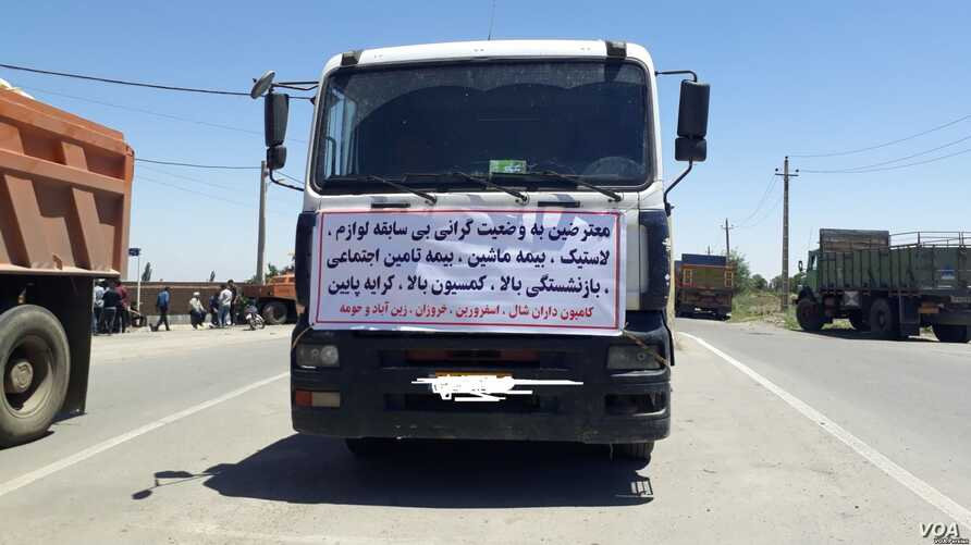 """A truck in the northern Iranian city of Qazvin displays a sign of a striking trucker driver on May 28, 2018. The sign reads: """"We are protesting the unprecedented high prices for spare parts and tires..."""""""