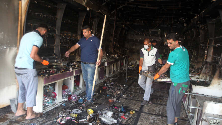 Iraqi men clear up a burned shop in Baghdad following two car bombs set off in mostly Shi'ite neighborhoods of the Iraqi capital, July 22, 2015.